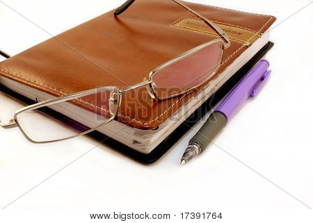 Diary and glasses on a white background