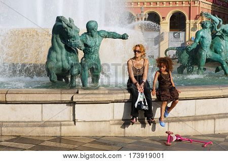 NICE, FRANCE - JULY 21, 2009: Unidentified people relax at the Fontaine du Soleil at the Place Massena square on a hot day in Nice, France. Place Massena is the main public square in Nice.