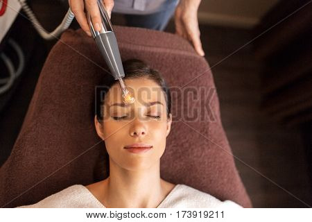 people, beauty, cosmetology and technology concept - beautiful young womans having face massage or mesotherapy by microcurrent firming massager in spa