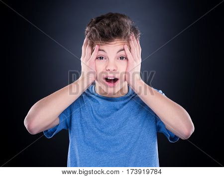 Emotional portrait of caucasian teen boy. Amazed teenager screaming looking at camera. Handsome surprised child, on black background.