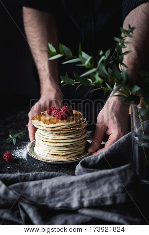 Stack of pancakes. Man hands serving pancakes with raspberries. Beautiful food still life. Natural light, slightly toned image