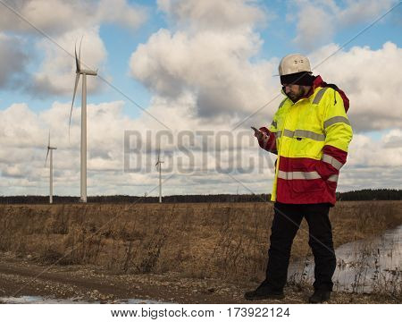 Full-length View Of Male Worker Using Phone Outdoors With Wind Tubes At Background.