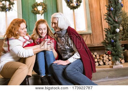 Happy family from three generations sitting on stairs and hugging while drinking hot tea