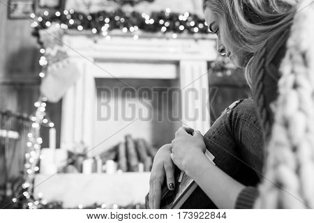 Thoughtful young woman sitting on floor with book at christmastime black and white photo