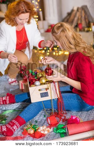 Happy mother and daughter sitting on floor and having fun with christmas decorations