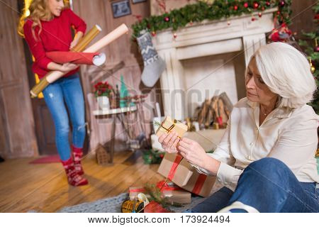 Beautiful senior woman sitting on grey carpet and wrapping christmas presents