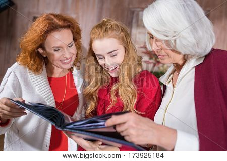 Smiling three-generation family looking at photo album