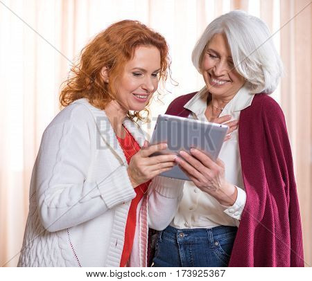 Two women using digital tablet and smiling