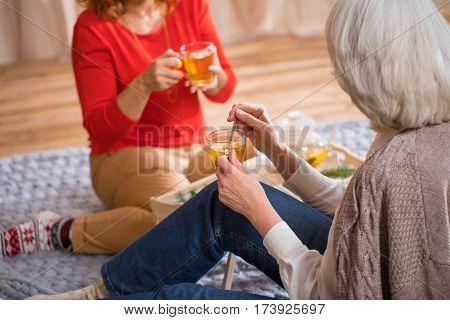 Two women drinking tea sitting on the floor