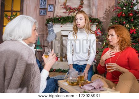 Family of three generations having tea time at home sitting on the floor near Christmas tree