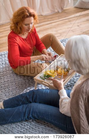 Woman sitting on the floor and pouring lemon tea in glass cups