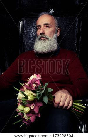 Close-up shot of a severe bearded man in black sitting in an armchair with a bouquet of flowers. The concept of congratulation, holiday