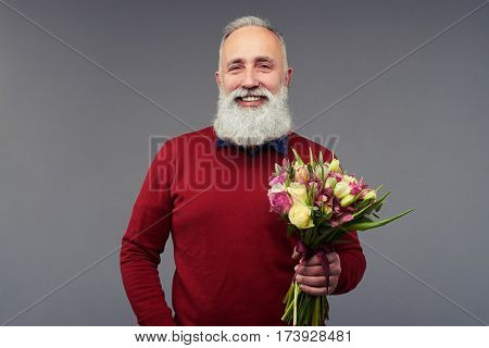 Close-up shot of senior bearded gentleman with a bouquet of flowers isolated over gray background in the studio. The concept of holiday and congratulation