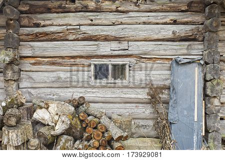 Heap of chopped logs for firewood near old wooden wall