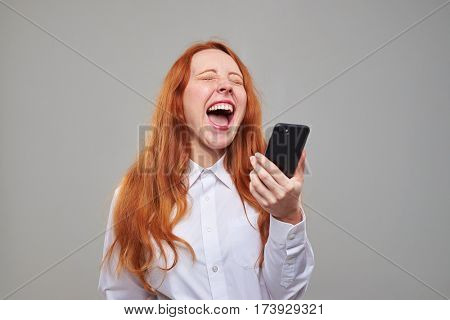 Close-up of red hair girl laughing while holding a mobile phone. Heartily laughing girl isolated over background in the studio