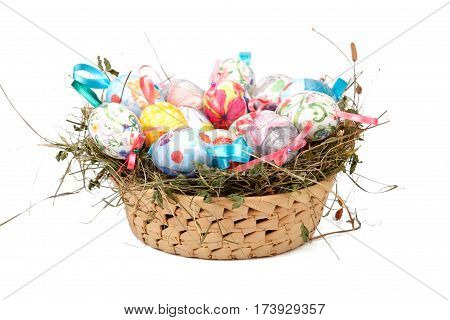 Close up of colorful Easter eggs in a basket isolated on white