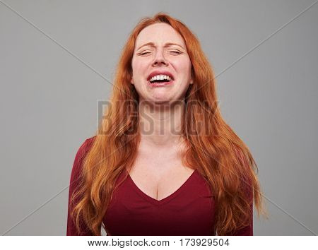 Close-up of redhead Caucasian woman disappointed and crying isolated over gray background. Facial expression reaction attitude to sadness