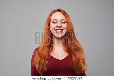 Close-up shot of happy woman with auburn hair looking at the camera. Toothy smiling. Woman with freckles and long cooper hair