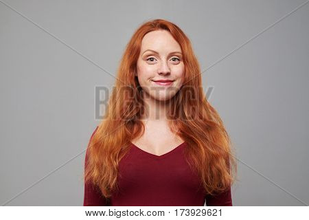 Close-up studio shot of elated red hair young woman with long red hair isolated over pink background