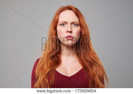 Close-up shot of dissatisfied woman with red hair over gray background