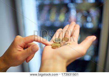 sell, technology, people, finances and consumption concept - hands counting euro coins at vending machine