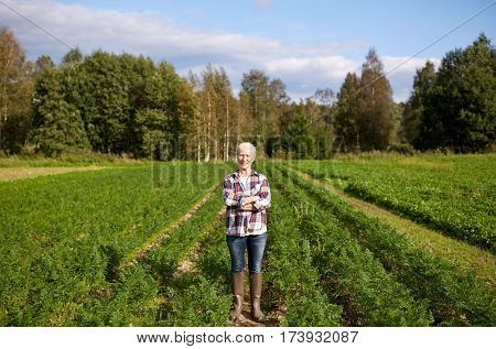 farming, gardening, agriculture and people concept - happy senior woman at farm