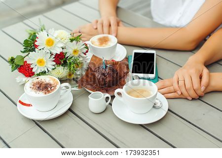 Chocolate muffin with one candle cups with coffee on the wooden table .
