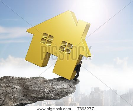 Man Holding Golden House On Cliff Edge