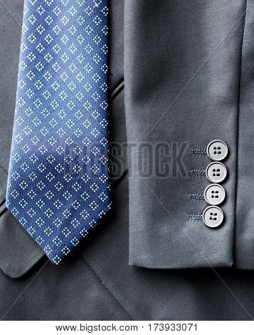 clothing, formal wear, fashion and objects concept - close up of business suit jacket and tie