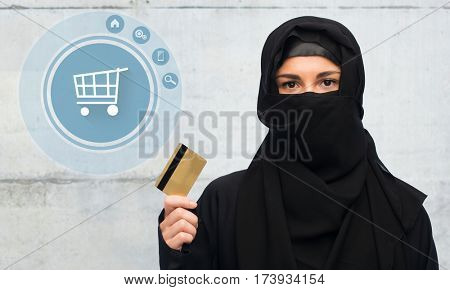 finances and people concept - muslim woman in hijab with credit card over gray concrete wall background