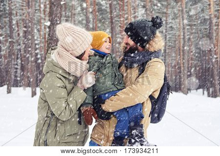Mid shot of young family laughing and holding son on hands during the stroll in the forest. Overjoyed family hugging during the walk in the forest on vacations