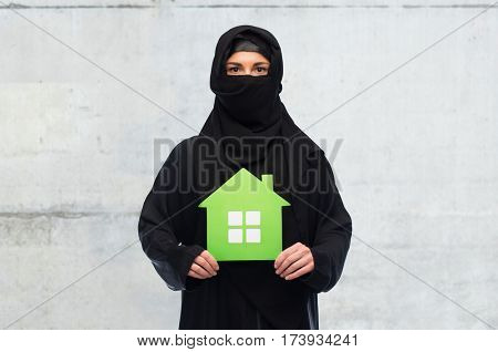 ecology and people concept - muslim woman in hijab with green house over gray concrete wall background