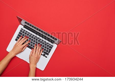 High angle of woman skinny hands working on a silver laptop on a red desktop and with copy space at right