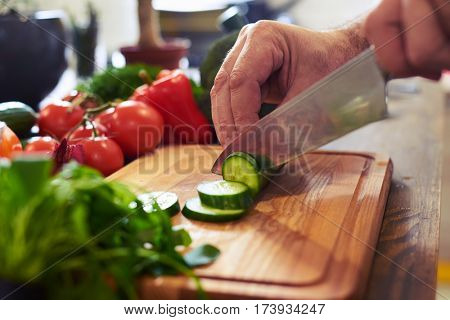 Crop shot of hands slicing cucumber on a cutting board. Healthy food. Preparing nutritious eating. Close-up of hands of chef cutting vegetables on wooden table