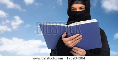 religion, education and people concept - muslim woman in hijab reading book over blue sky background