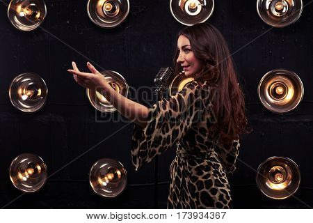 Side view of tempting woman beckoning with hand singing in a microphone over spotlight. Wearing a sexy leopard dress. Pretty girl with evening makeup and loose curly hair