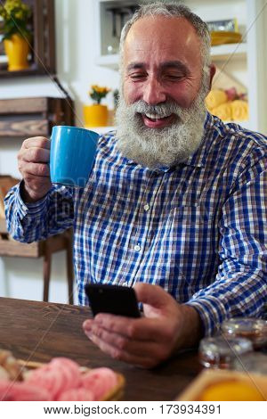 Close-up of mature man enjoying a cup of tea. Sitting at the table in the kitchen. Texting via smartphone. Wearing checked shirt