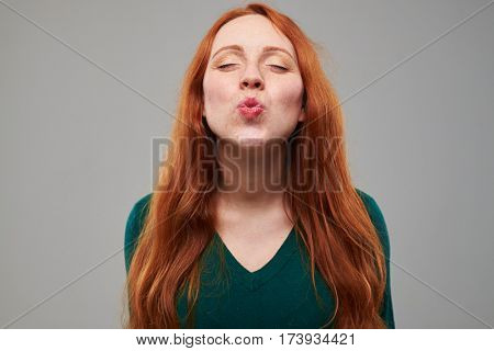 Close-up shot of delightful young girl puckering lips at the camera. Giving a kiss. Lovely lady isolated over gray background in the studio