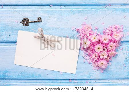 Heart from pink flowers and petals empty tag and vintage key on blue planks. Selective focus. Place for text.