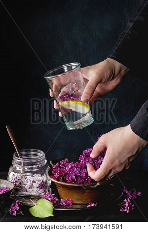 Female hands hold glass of lilac lemonade with lemon. Glass jar of sugared lilac flowers and vintage bowl of fresh flowers on black tablecloth over black. Dark rustic atmosphere. See series.