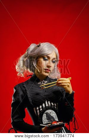 Pretty old-fashioned girl posing with suchi over red background