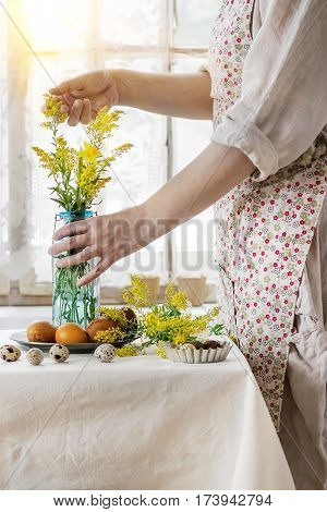 Preparing for Easter. Female hands holding yellow flowers near white tablecloth table decorated brown chicken and quail colored easter eggswith window as background. Day light.