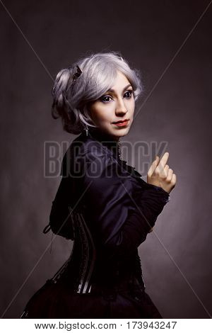 Gothic old-fashioned girl posing over dark background