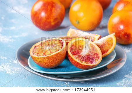 Sliced and whole ripe juicy Sicilian Blood oranges fruits on ceramic plate over blue concrete texture background. Selective focus