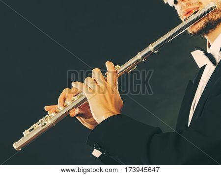 Classical music passion and hobby concept. Elegantly dressed musician man playing on flute wearing black fedora hat. Studio shot on dark grey background