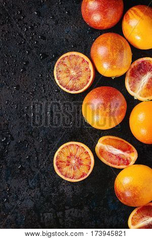 Sliced and whole ripe juicy Sicilian Blood oranges fruits on black wet metal texture background. Top view with space