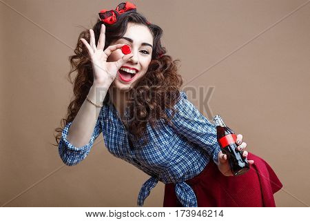 Happy Beautiful Pin Up Girl Holding Cup of Glass Bottle as OK Symbol and Giving you a Soda. Woman Dressed in Red Skirt and Blue Plaid Shirt.