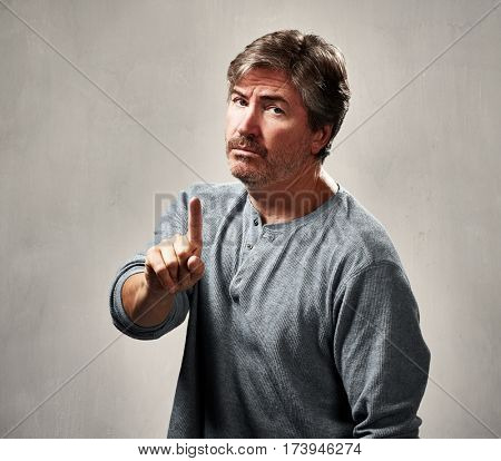 Disapproval refusing man gesture over gray wall background