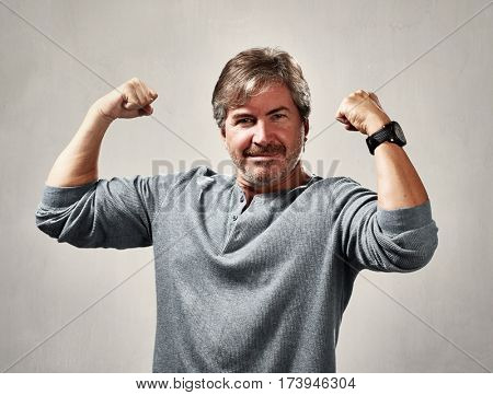 Strong powerful man over gray wall background
