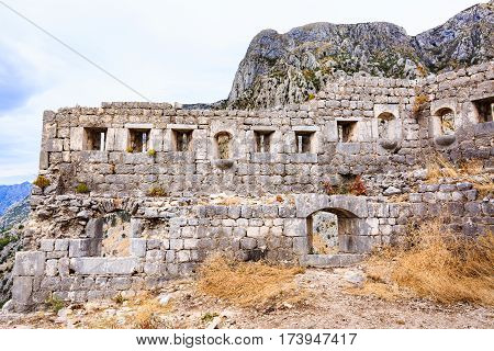 Old stone walls of medieval fortification, town ruins against Lovcen mountain in Kotor, Montenegro.